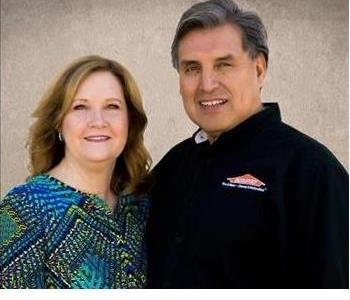 The owners smiling in front of a cream background.